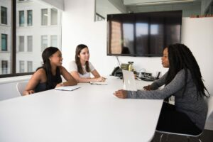 a group of female office workers discuss an issue in a meeting room at a white table