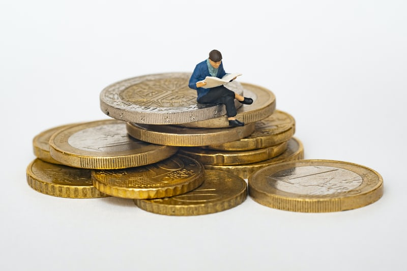 A man sitting on a stack of coins symbolising the gig economy