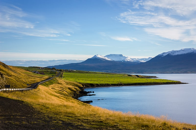 A lake in Iceland with mountains in the background under a blue sky