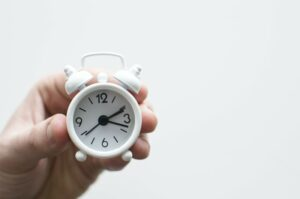 A close up of a small white alarm clock showing individual time management in the gig economy