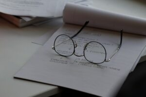 A pair of glasses resting on a piece of note paper in an office