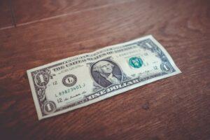 A singular one dollar bill on a brown table top