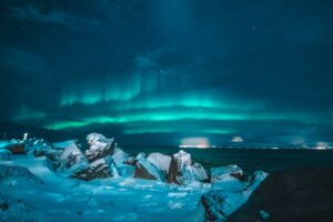 The Northern Lights in Iceland over the ocean with snowy rocks in the foreground