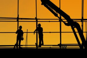Two men silhouetted on a construction site