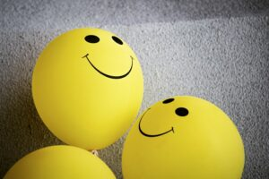 Yellow balloons with smiley faces on them