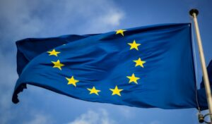 The EU flag waving against a blue sky background