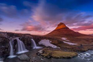 Kirkjufell mountain inn Iceland with the sun setting behind it