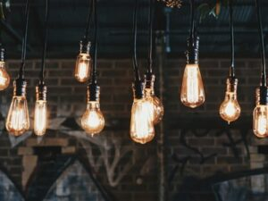A series of bright lightbulbs hanging from a dark ceiling