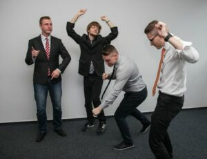 Four men dancing at an office party