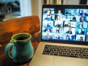 A remote worker on a zoom meeting from home with a cup of coffee