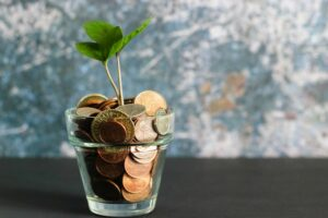 A a cup of pennies with a plant in it symbolising personal savings