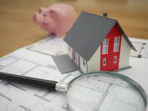 A piggybank, house and magnifying glass symbolising saving money to move to Iceland