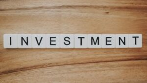 Investment spelt out with scrabble pieces on a wooden table