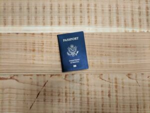 A blue American passport on a wooden bench