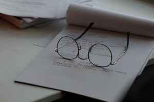 A pair of glasses resting on a sheet of white work paper