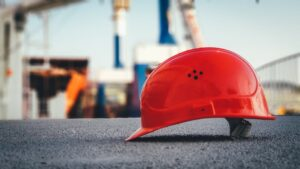 A red builders hat on the gravel at a building site