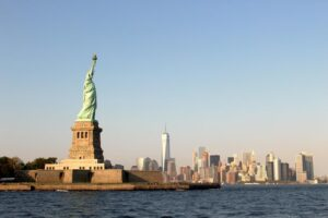 The statue of Liberty and Manhattan skyline under a blue sky