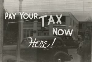 A sign on a window telling people to pay their taxes