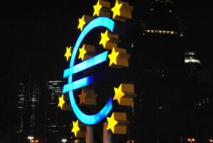 A fluorescent neon sign of the euro currency symbol at night