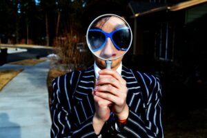 A man holding a magnifying glass to symbolise looking for a job in Iceland