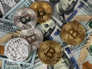 Bitcoin currency on top of a pile of US dollars