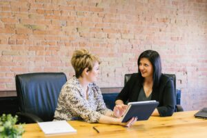 two female employees discussing project results in a boardroom with a red brick wall behind them