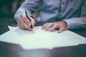 a close up of a man signing an employment contract