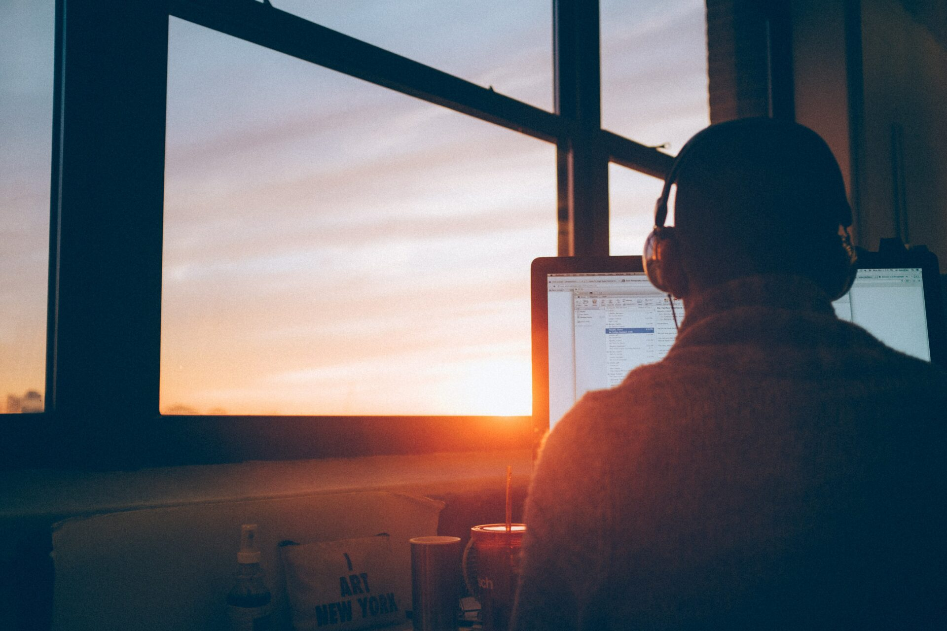 A remote worker looking at a sunset out the window