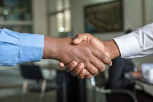 a close up of two office workers shaking hands